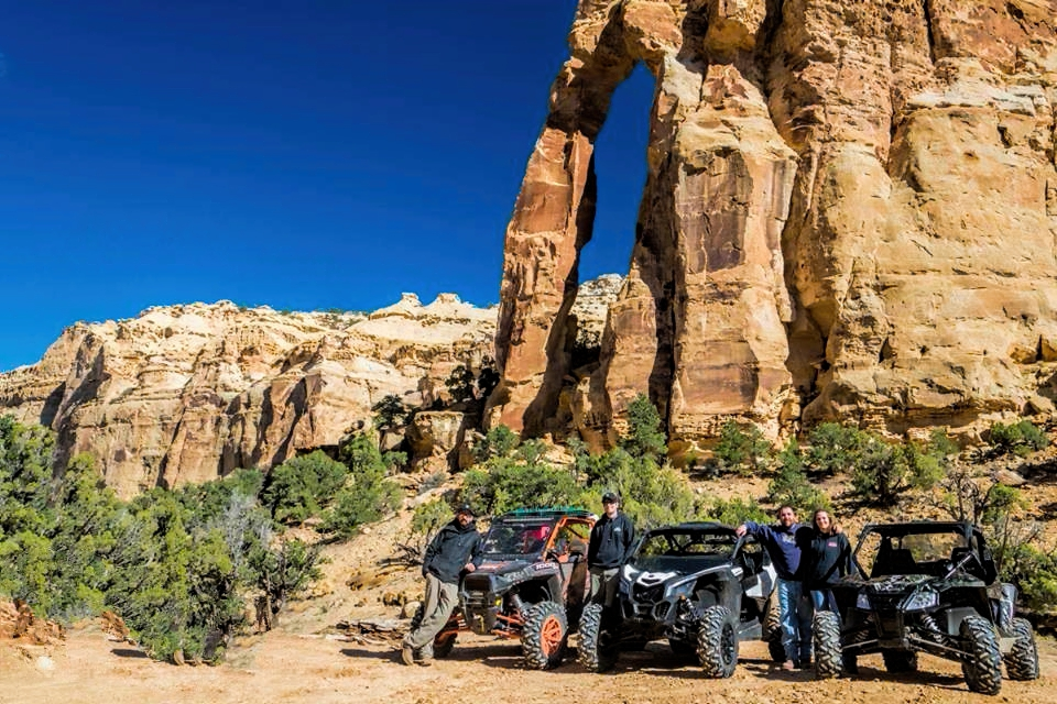 Desert setting, group of people standing besides ATVs