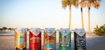 beer cans on the sand with palm trees in background