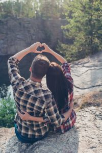 Good shiny morning in wood! Rear back high angle view of two people in love, wearing casual, sitting on the top of canyon stone rock, embracing, making heart shape with hands