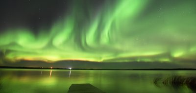 An image of glowing Northern Lights reflecting on a lake.