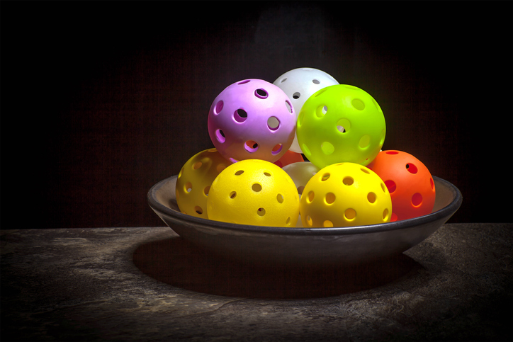 Colorful still life of yellow, green, red, pink & white Pickleballs in a bowl with dark background