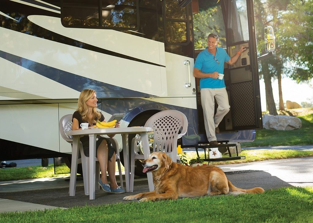 Couple chatting at table outside of large RV