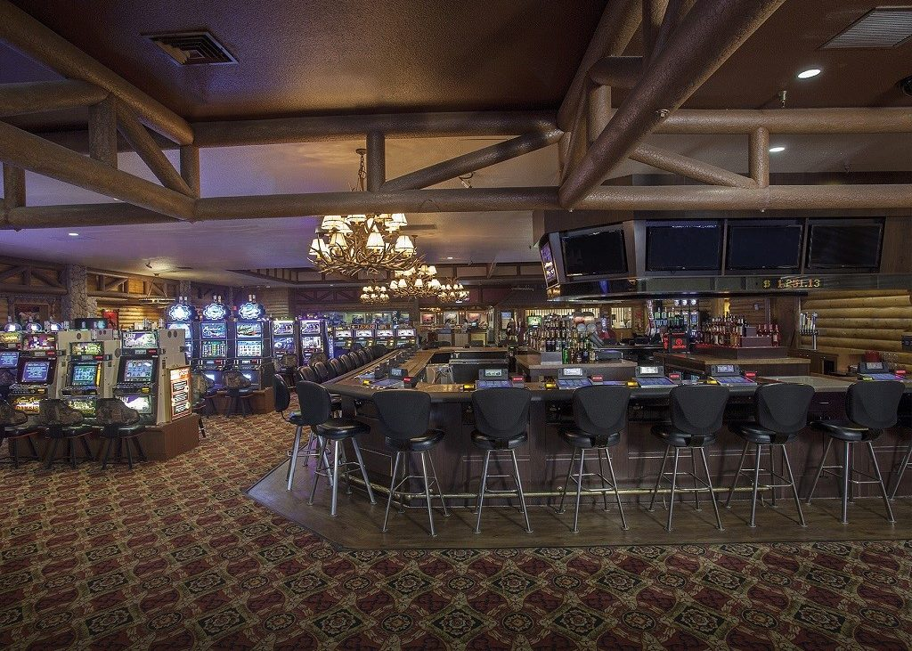 Interior view of bar at casino with slot machines in background