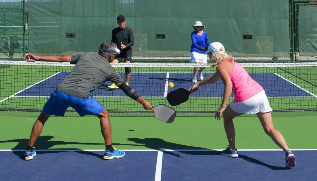 Multiple people playing pickleball during the day