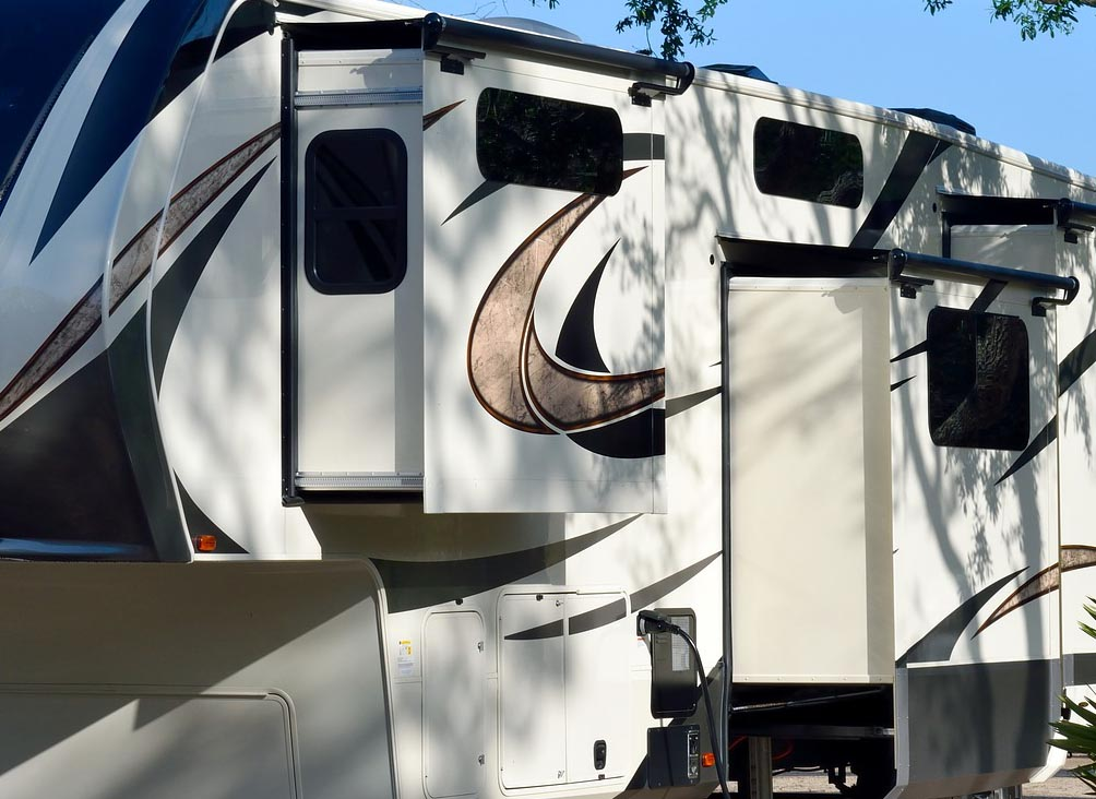 Extended RV slideouts in a shady campground.