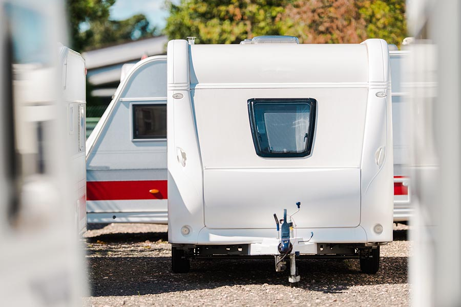 RV travel trailers packed tight in an outdoor storage lot.