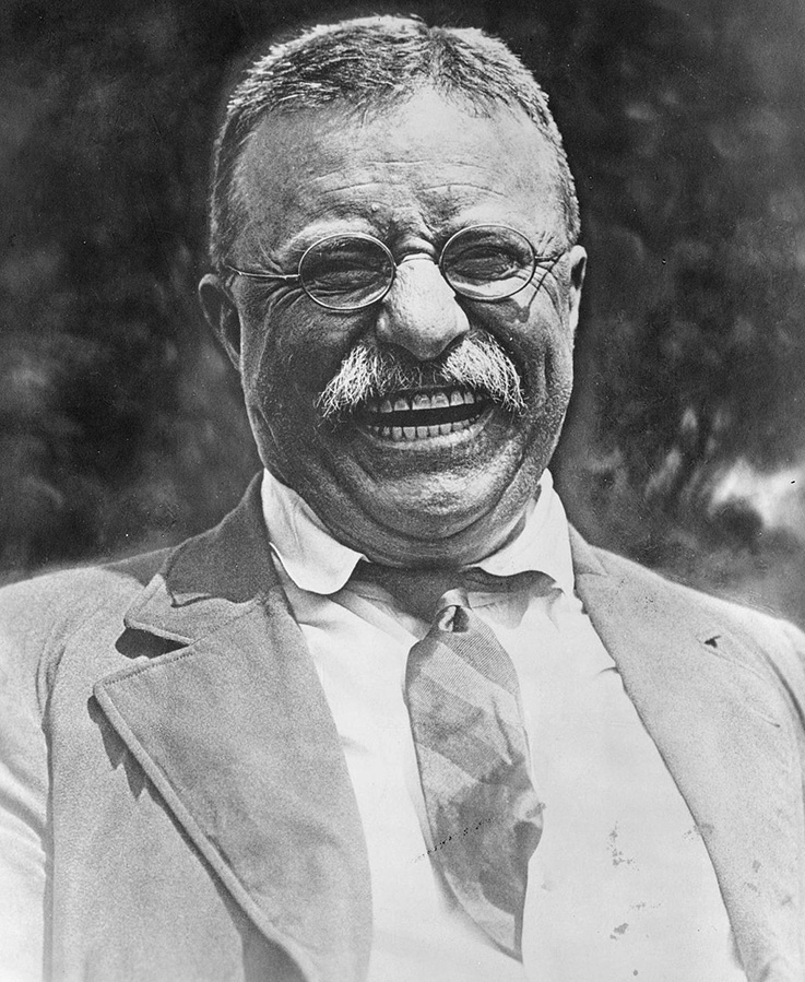 Theodore Roosevelt grins and laughs.