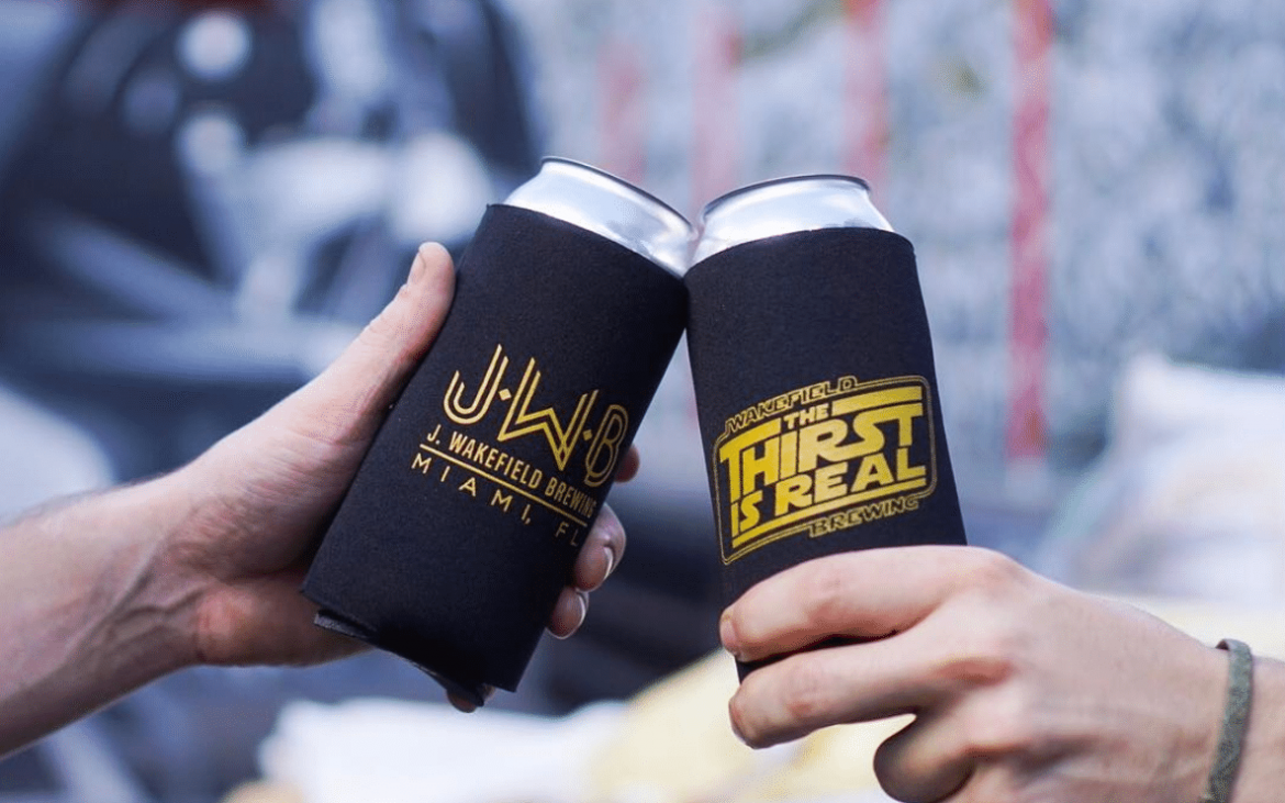 Hands cheering canned beers in koozies