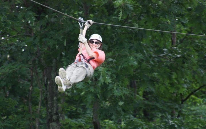 Camper zipping down a zipline