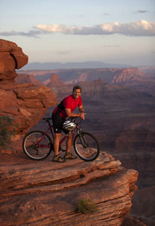 Man sitting on top of bicycle on edge of cliff in Canyonlands National Park