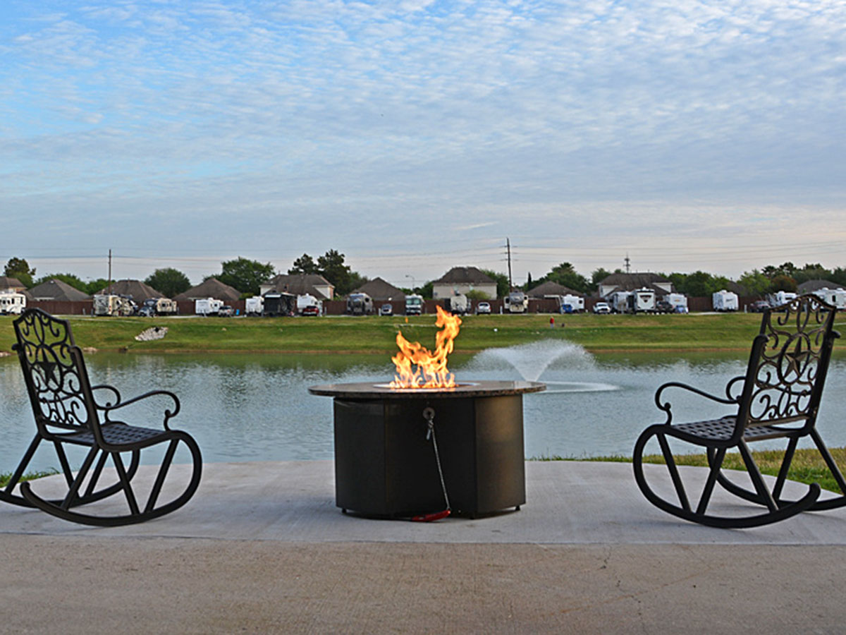 two rocking chairs beside a firepit with large fountain in backdrop.