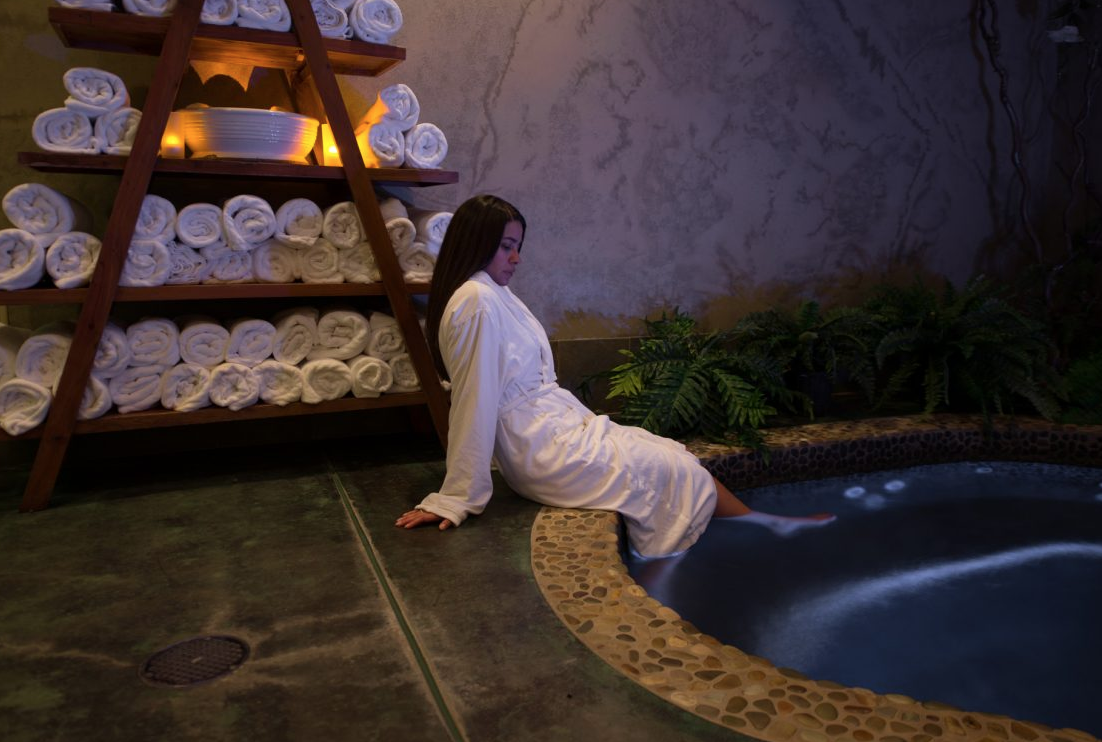 Young woman sitting on edge of jacuzzi in a bathrobe with her feet in the water.