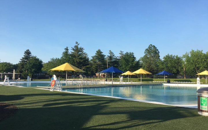 Clean pool at RV Park with umbrellas around parameter.