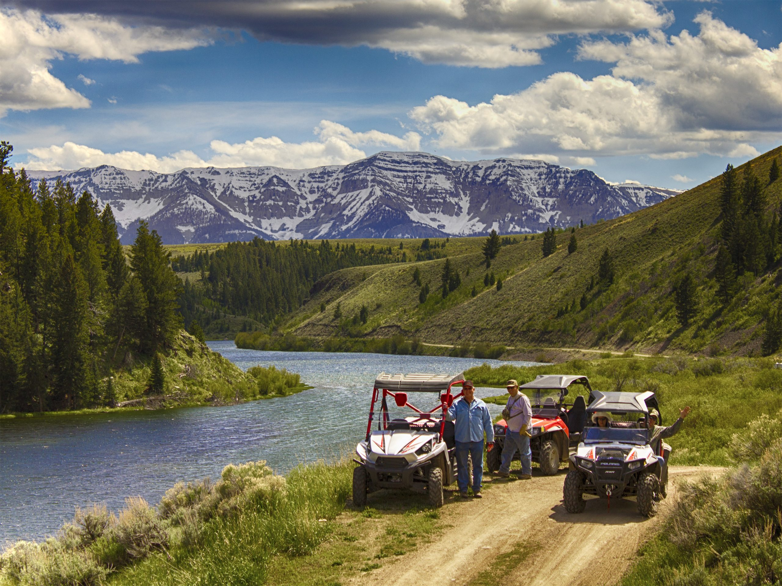 Off road vehicles along river in the mountains