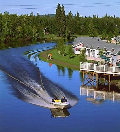 Yellow speedboat cruising down a river alongside homes.