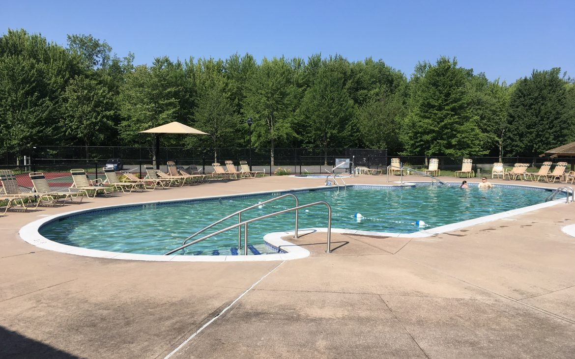 Large community pool with surrounding lounge chairs
