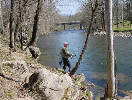 Man standing at edge of river bank fishing