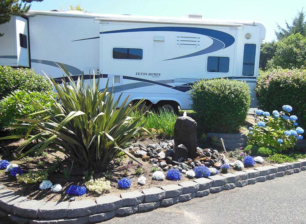 White RV with violet and white flowers