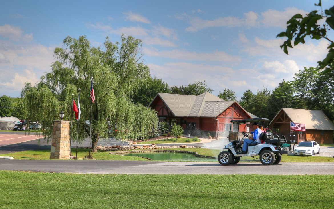 Golf card cruising past bright red barn-style front office