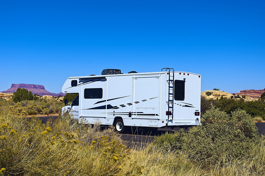 Motorhome parked on road in desert with yellow and brown brush