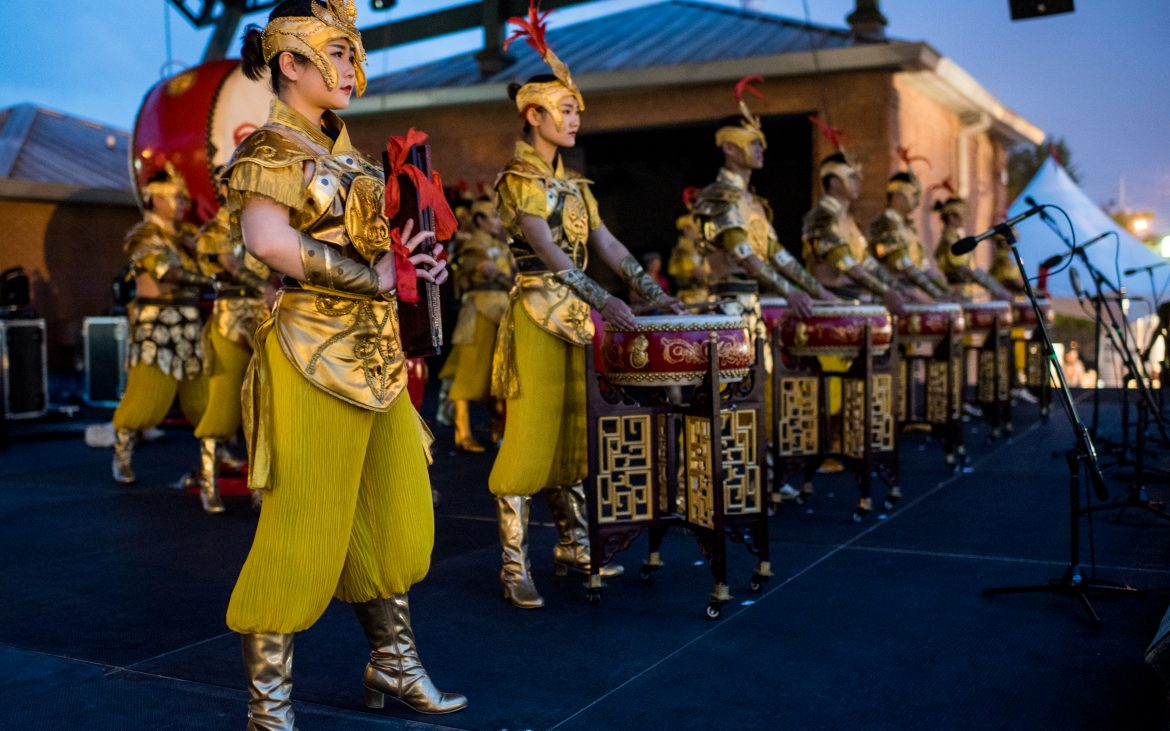 Performers on stage with hand drums dressed in yellow garb