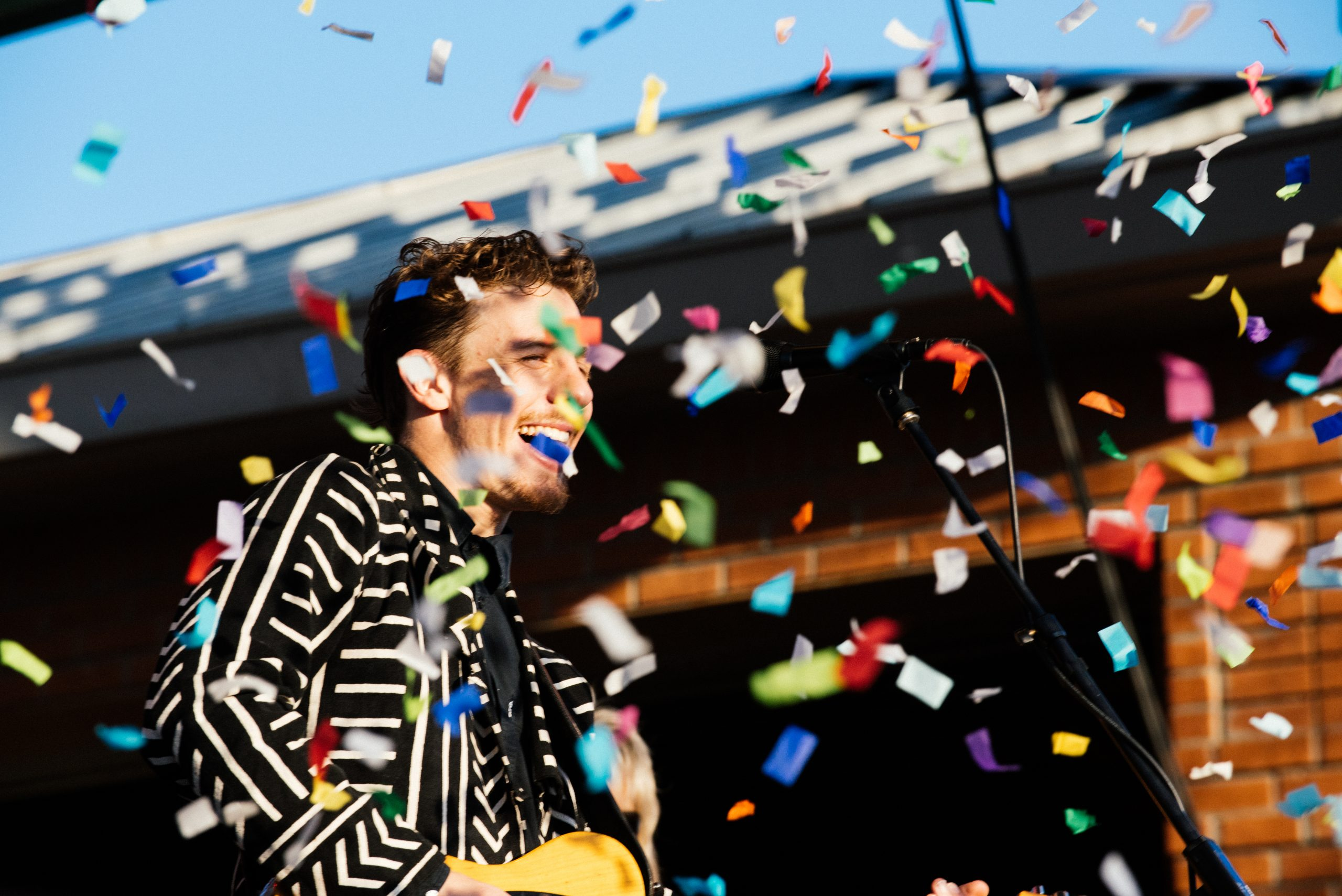 Performer in black and white jacket on stage with confetti flowing