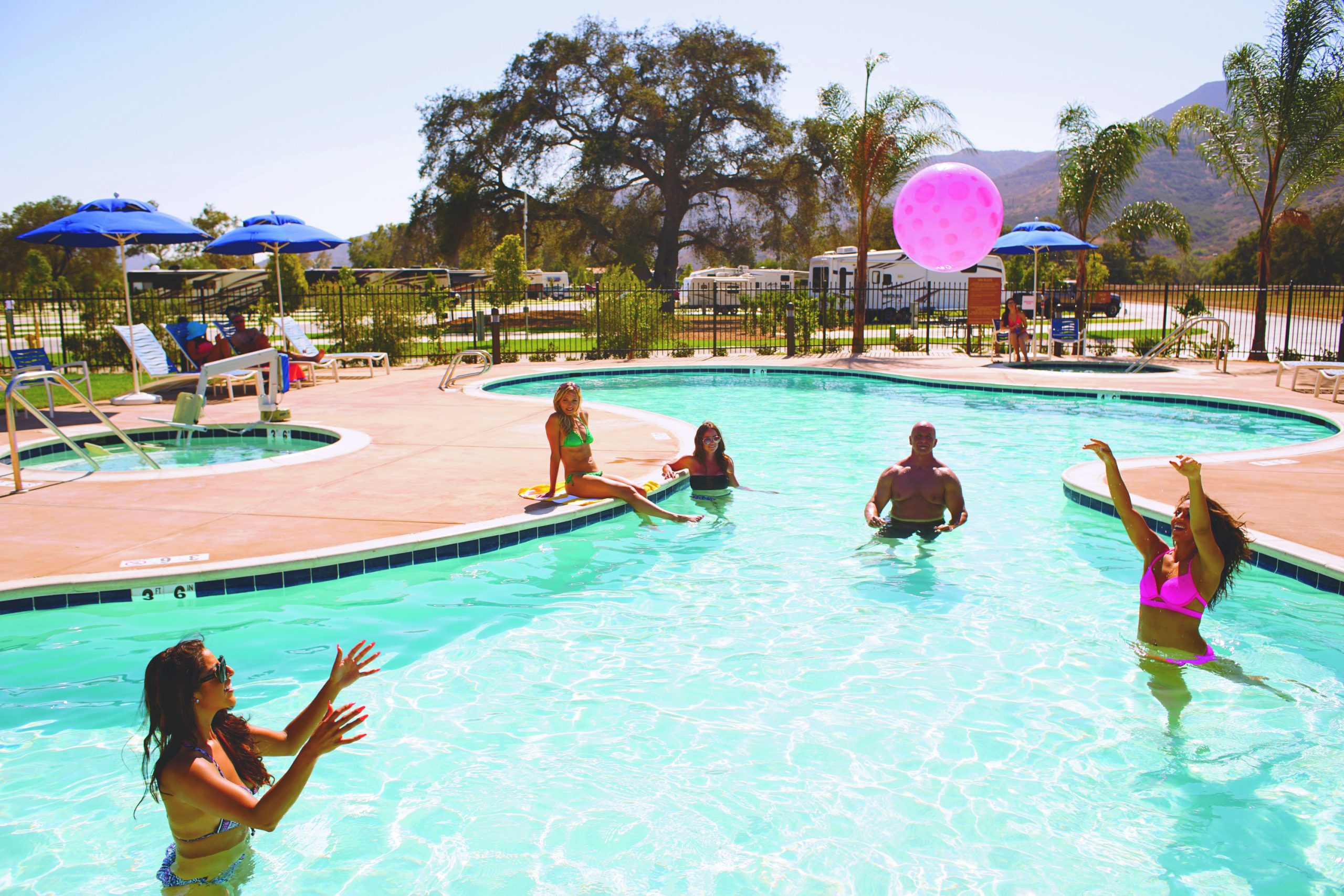 People playing in crystal clear community pool