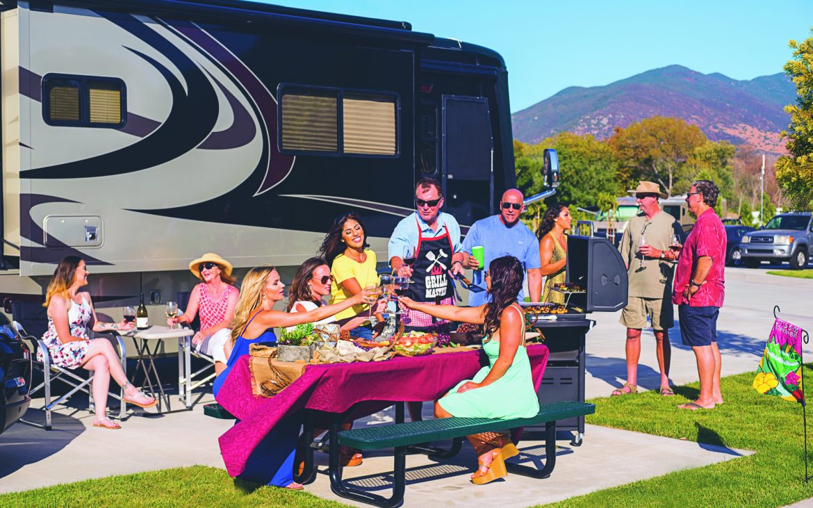Large family enjoying food around picnic table beside RV