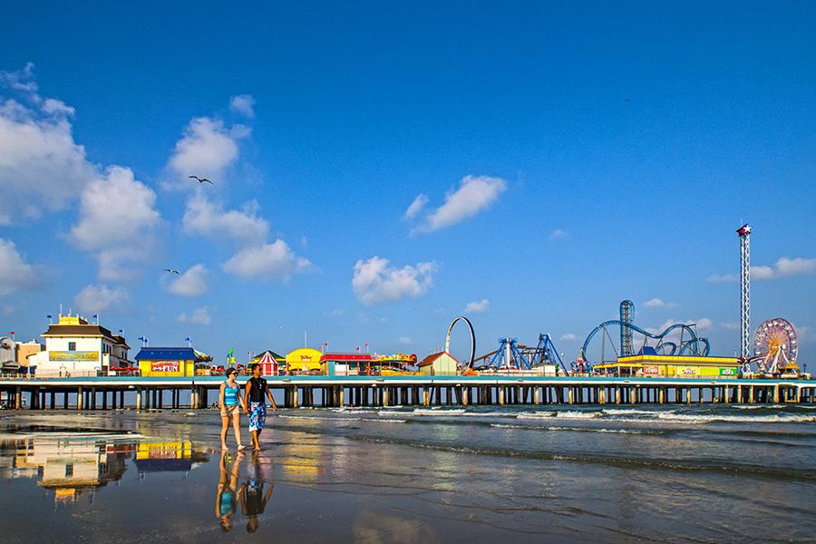A couple walks on the beach near Galveston's Pleasure Pier.