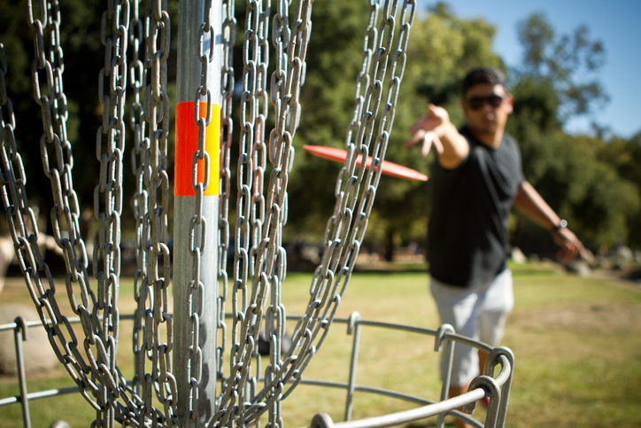 Disc golfer releases disc towards the basket for a successful putt.