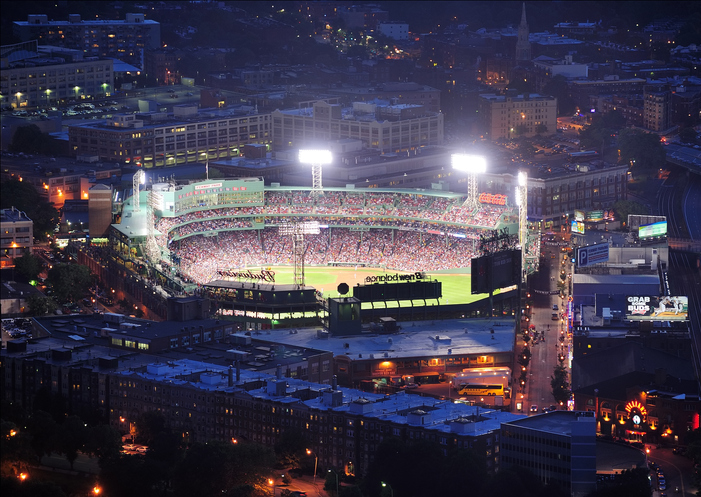 """Boston, Massachusetts, USA - June 20, 2011: Fenway Park stadium aerial view at night illuminated by lights with base ball game going on."""