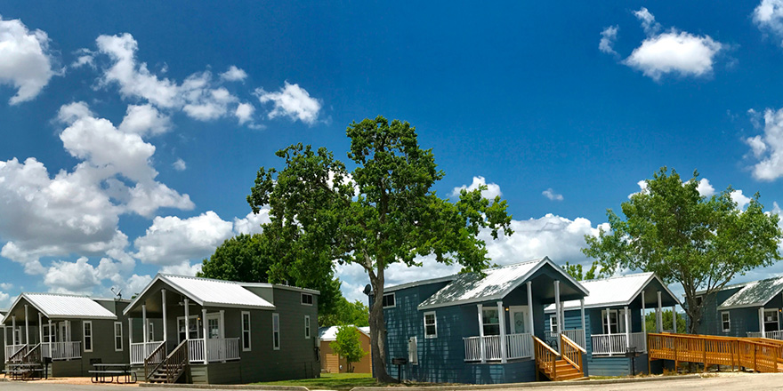 A pair of Sun RV Hill Country cottages under a blue Texas sky.