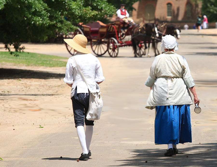 Costumed reenactors walk the streets of Colonial Williamsburg.
