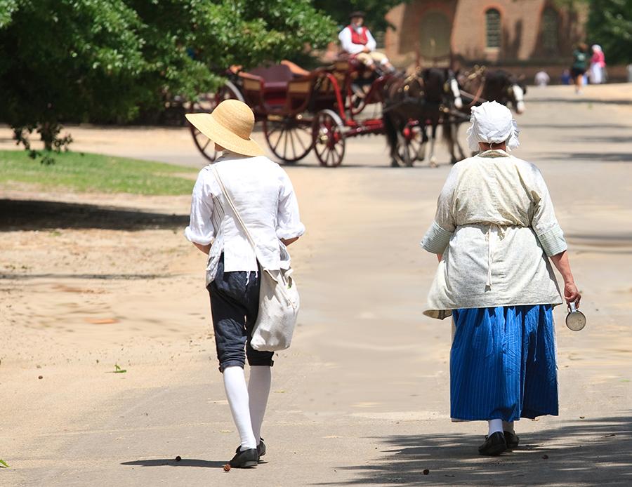 Costumed reenactors walk the streets of Colonial Williamsburg.