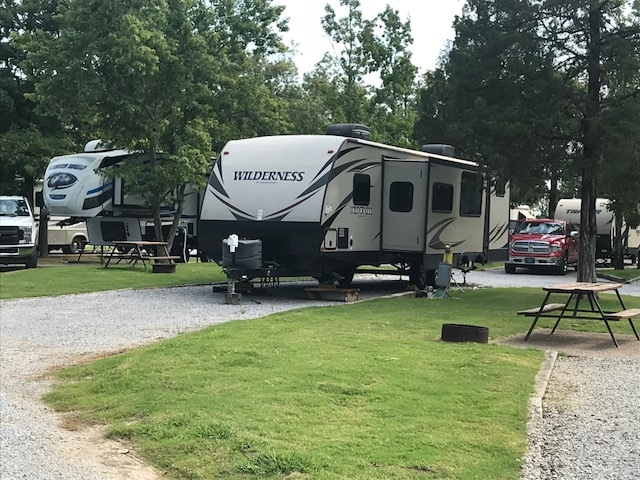 Large gray and brown trailer backed into RV spot at campground