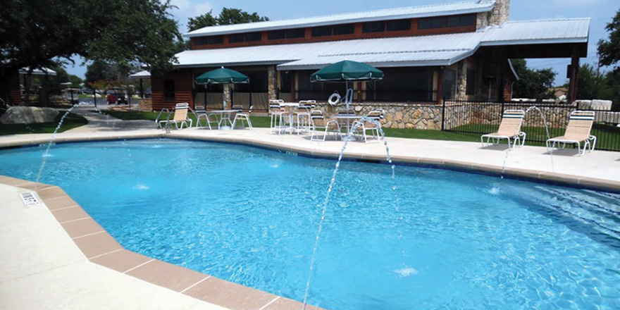 A pool with deck chairs and structure at in the La Hacienda RV Resort.