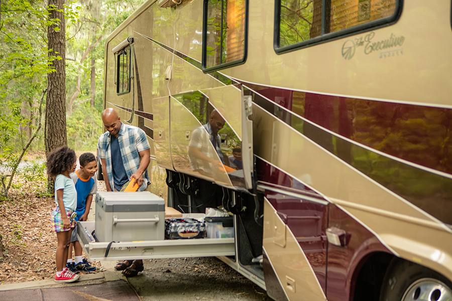 A father and two children unpacking a motorhome at an RV park.