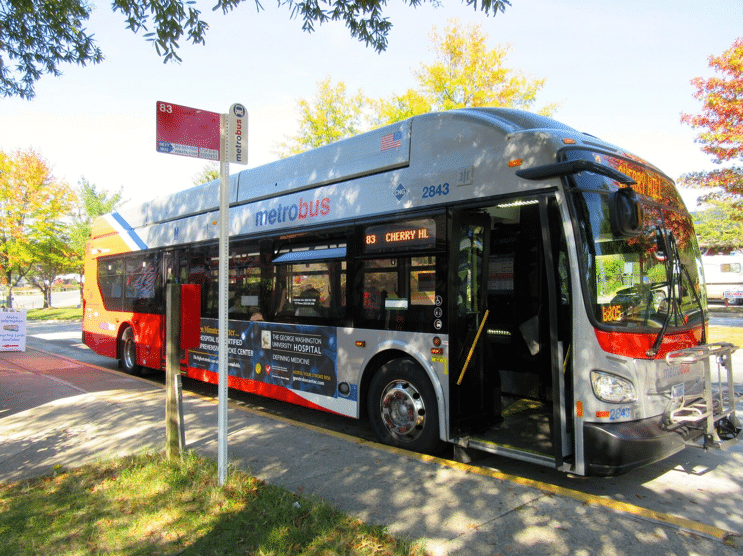 Large gray and red public bus