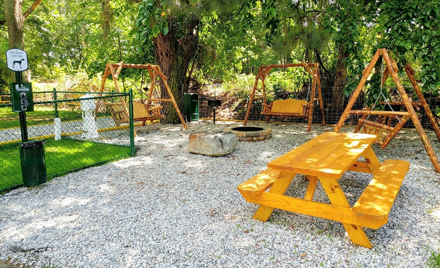 An RV site with a dog run, three swingsets and a picnic table.