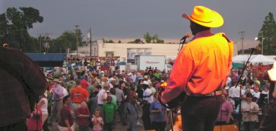 Man in yellow shirt and hat addressing a crowd