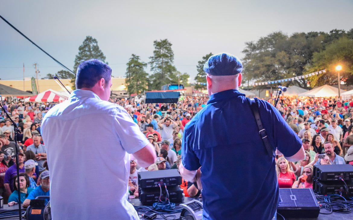Two men playing to a crowded fair from stage