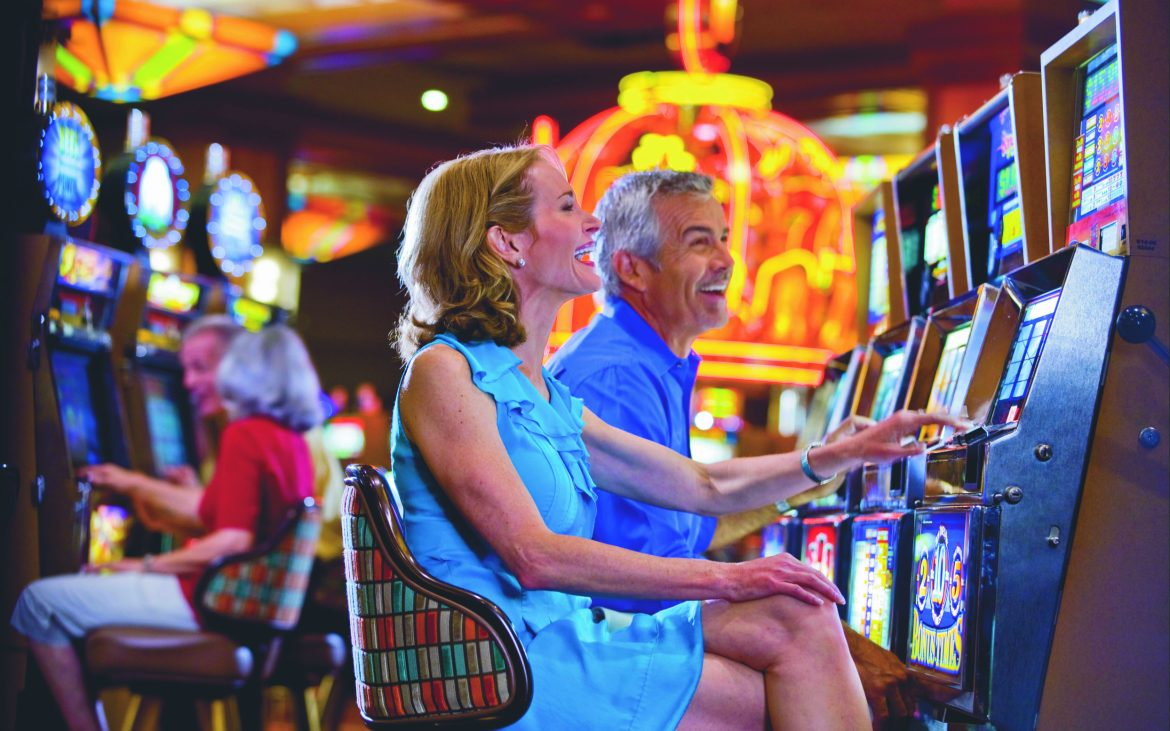 Couple playing slots in large colorful casino