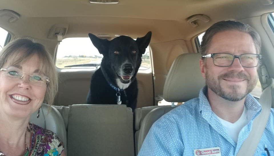 A smiling couple in vehicle with a dog in the back seat.