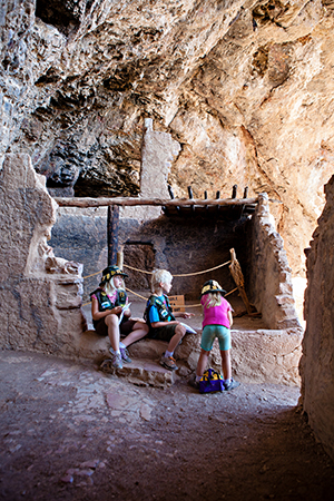 Three kids in the Tonto National Monument amid Native American ruins.