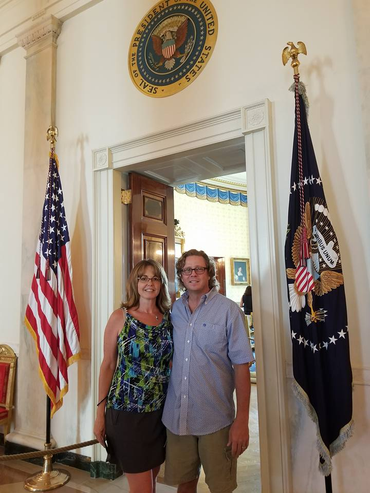 A couple stands beneath the presidential seal and are flanked by the U.S. flag and President of the United States Flag.