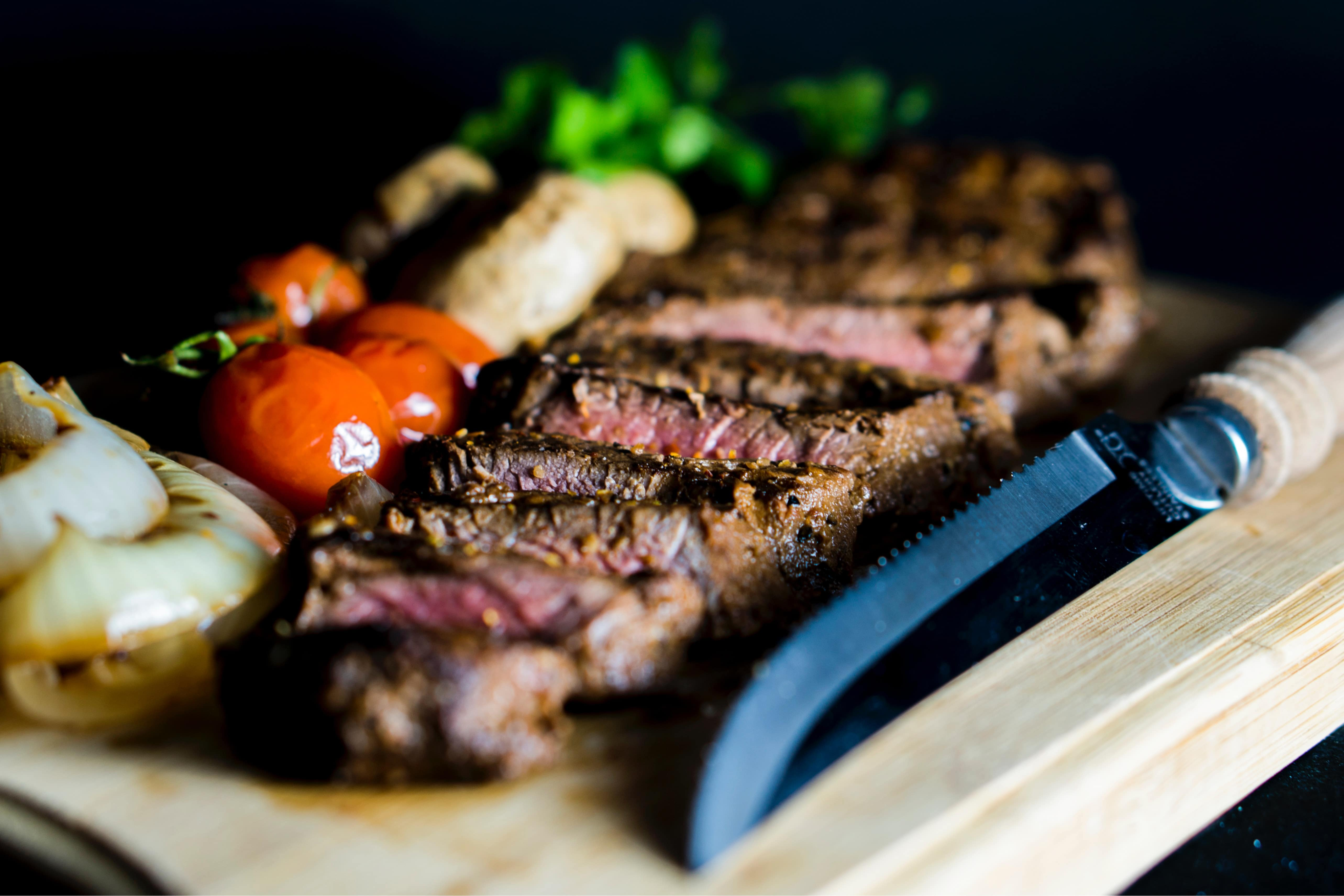 A steak on a cutting board with vegetables.