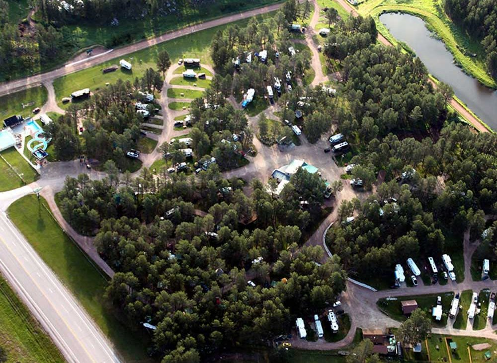 Breathtaking aerial view of Beaver Lake campground with lush trees and pond in background