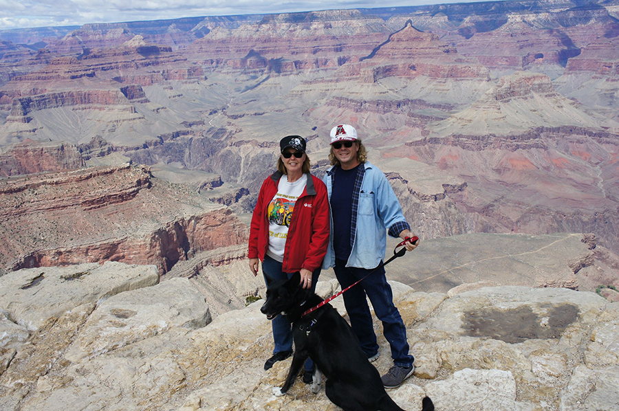 A couple with dog on the rim of the Grand Canyon.