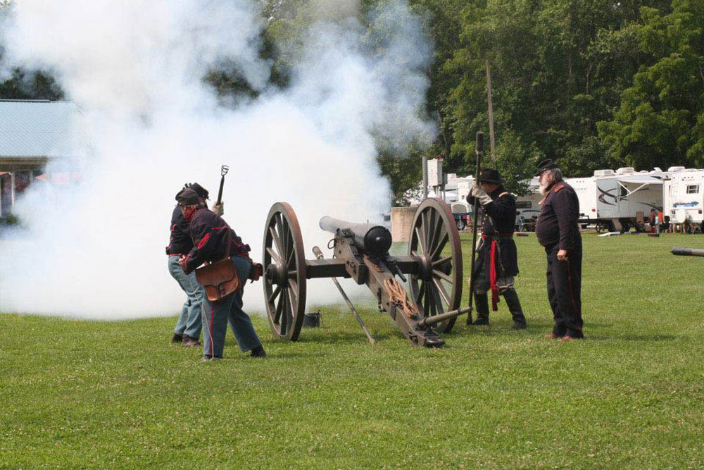 Men participating in firing a canon during civil war reenactment