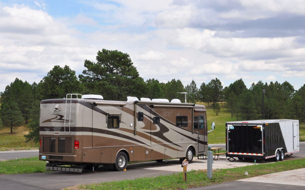 Tan and brown RV parked at campsite